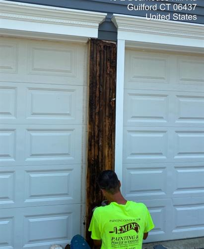 Carpentry fixes this rotted piece of siding between garage doors.