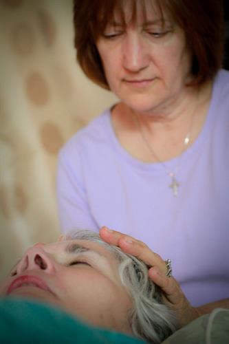 The hands are placed over each of the major chakras (energy centers) of the body to balance the client's energy.