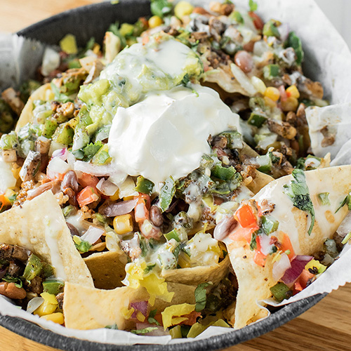 Nachos - Crispy chips, your favorite toppings, then smothered in white cheese dip