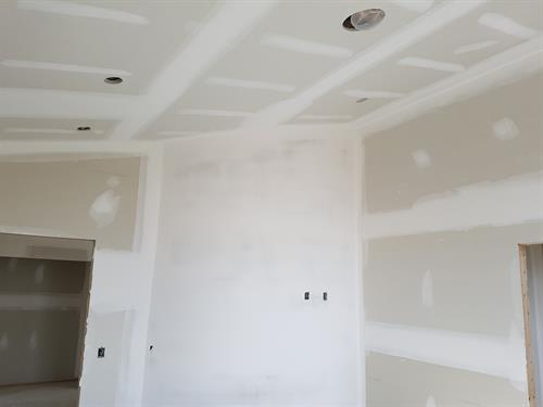 Taping and coating a new home with curved wall in living room Airdrie