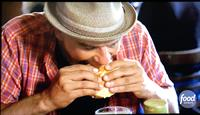 Michael diving into Our Famous Olive Burger
