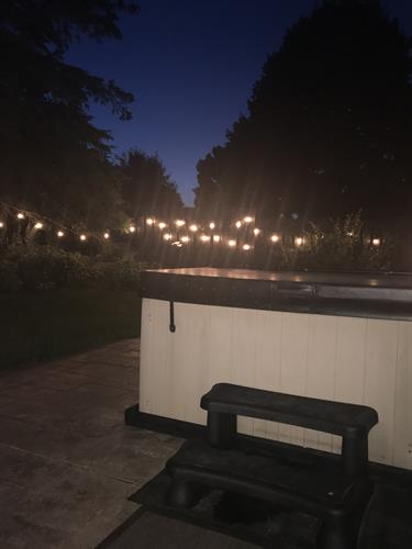 Our hot tub outdoors under the stars or edison lights