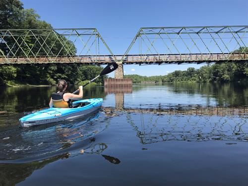 A kayaker enjoys the serene waters of the Hudson by the historic Dix Bridge.