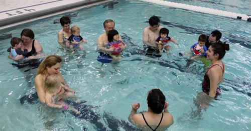 Children and their caregivers participate in a lesson at free a Water Safety Event