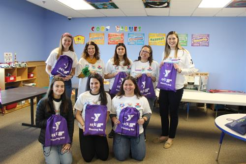 "Y staff and volunteers hold up ""blessing bags"" created for Second Step families"