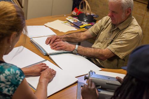 A middle-aged man learns braille at The Carroll Center for the Blind.