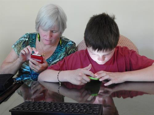 Assistive technology can help blind and visually individuals of all ages and stages. Here, a teacher of the visually impaired coaches a young boy in how to use his phone to assist in schoolwork.