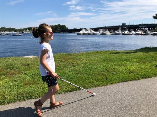 This young girl holding her white cane walks along the Charles River after receiving orientation and mobility training.
