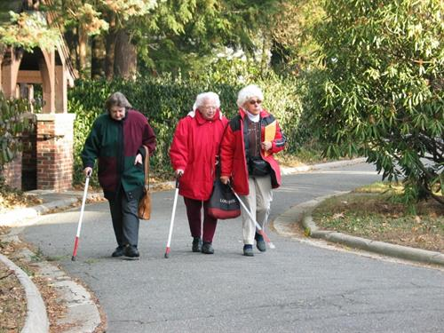 Seniors walk up the Carroll Center driveway after purchasing high visibility canes at the Carroll Center Low Vision Store.