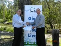 Michael Salter from Albury's Adroit Insurance Group presents donation to Gerard Van Emmerik following the 2013 Charity Golf Day