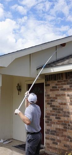 cleaning eaves of wasp nest and spider wbbing