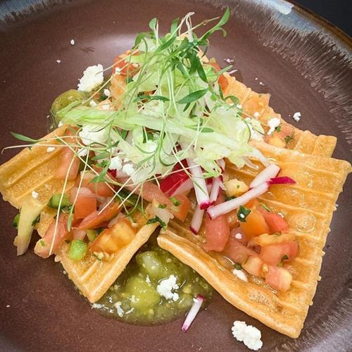 Crispy Chicaron Skin Chips sitting on a our fresh roasted tomatio salsa verde and topped off with pico de gallo, lettuce and queso fresco