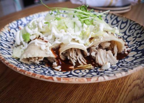 Our savory Mole Enchilada. Stuffed with moist pulled chicken, shredded queso fresco all in a hand-made corn tortilla and topped off with lettuce, sour cream, an cilantro