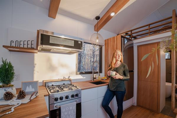Gallery Image Fritz_Tiny_Homes_Heather_in_the_tiny_house_kitchen_looking_out_the_window.JPG