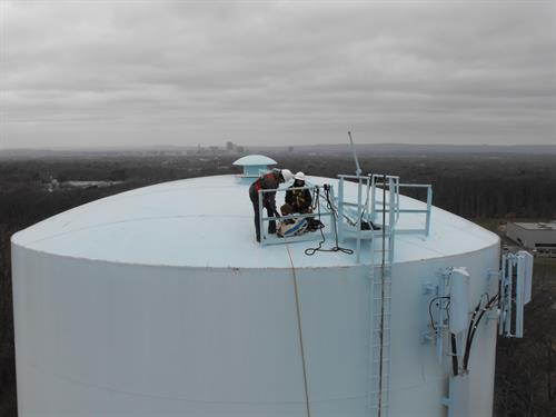 CorrTech technicians inserting ROV inspection vehicle into water storage tank