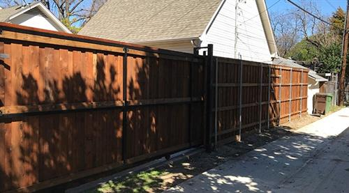 Commercial sliding gate with cedar board on board fence