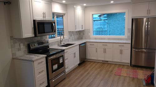 Kitchen remodel - new flooring, wall removal, new window, new cabinets, tile backsplash, new paint and trim