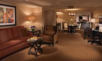 Our Presidential Suite features a spacious living room with dining area, and a private bedroom with king-size bed and flatscreen TV.
