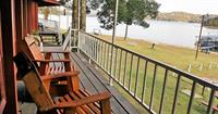 Cabin porch view with glider rockers overlooking the lake