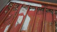 An unsucessful attempt has been made to patch a corroded steel tray roof. The roof sheeting needs to be relaced