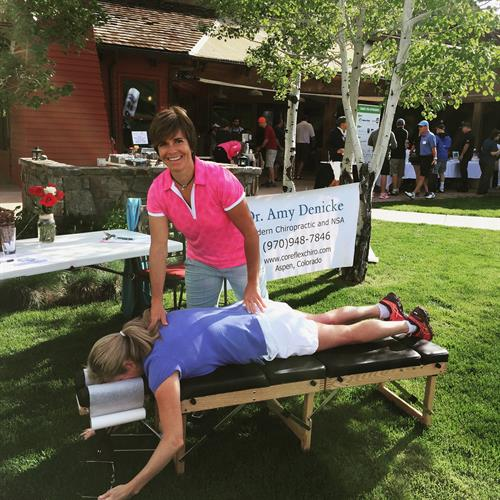 Dr. Amy serving chiropractic at a charity golf tournament