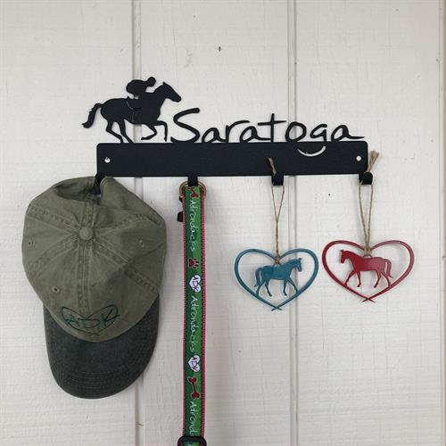 Saratoga text on a metal sign with a jockey riding a horse.  This wall mount has 4 hooks to hang keys, ball caps, dog leashes.