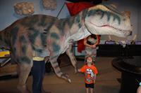 Young museum visitor shakes hand with miSci's Dino mascot during the exhibit opening of Return of the Dinosaurs