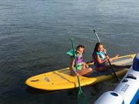 Cousins enjoying paddleboarding on the lake