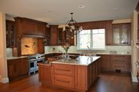 Cherry transition kitchen featuring fossil backsplash. Design by Arthur Zobel