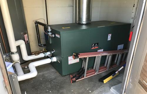 Installation of a new RayPak boiler with storage tank.