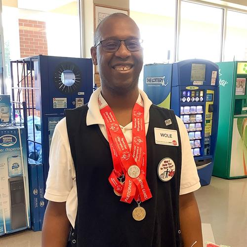 Riverside client working at Big Y, showing Special Olympic winning medals
