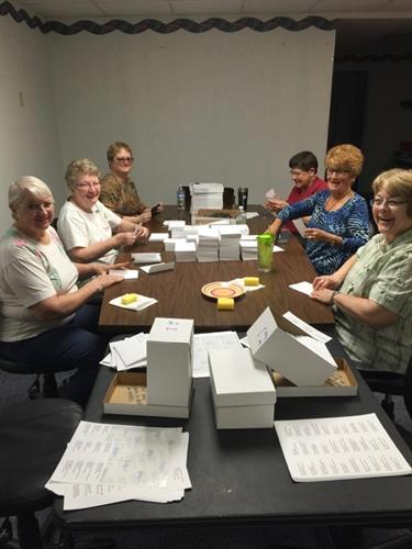 Volunteers help with mailings, the wine tasting, and many other projects.