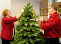 """Donita Wolf, director and Larry Schumacher, chaplain placing memorial angels on the """"Tree of Life"""""""