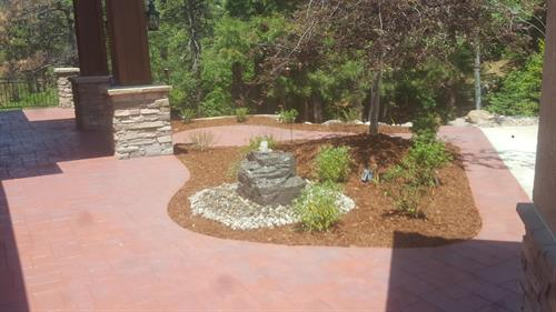 Pondless water feature, planting topped off with fresh mulch