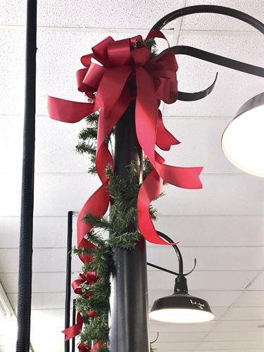 Ribbons and Garland on grocery aisle light posts at Christmas