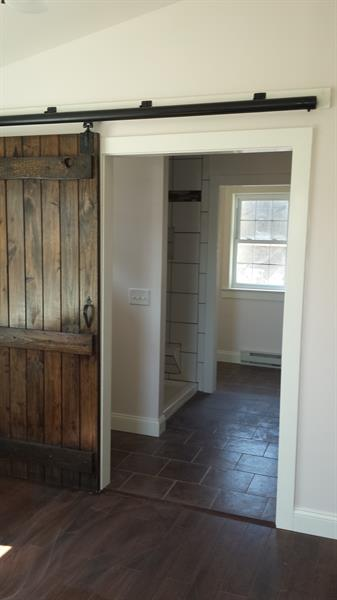 Addition with custom made barn style door that closes off bathroom and laundry area