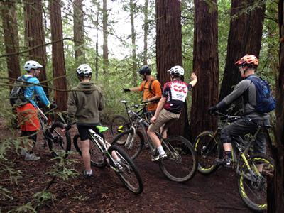 Evaluating the terrain in advanced mountain bike clinic