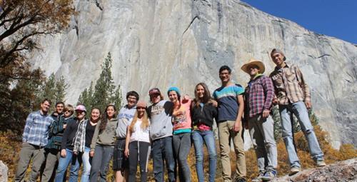 A weekend retreat cohort poses beneath El Capitan in Yosemite Valley