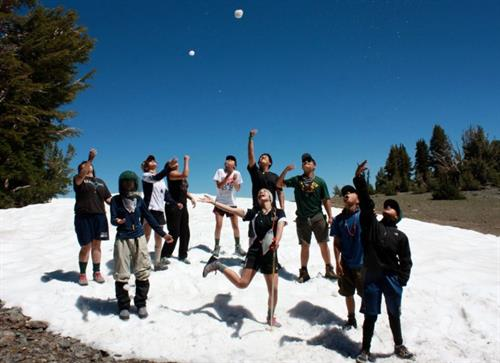 Summer course students enjoy some play on a snow patch leftover from the big 2017 winter