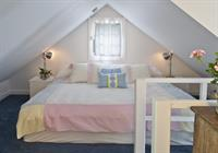 King bed in the upstairs sleeping loft with a separate sitting/dressing area