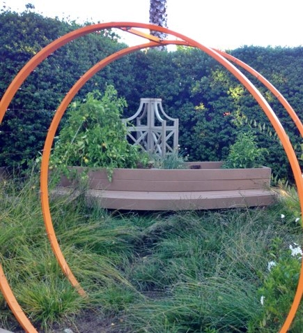 Custom Arch with natural grasses lead to a curved bench and raised veggie bed planter.