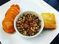 Black eyed peas with turkey ham and white jasmine rice, sliced sweet potatoes with a honey butter sauce and warmed cornbread.
