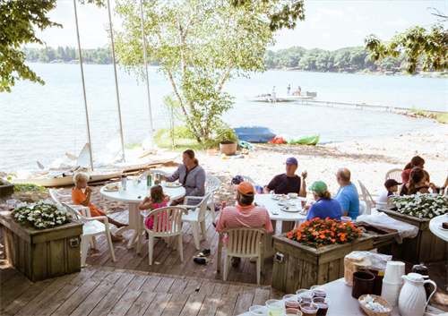 Guests dine on the deck for lunch. The summer all-inclusive program provides 3 meals and day and activities!