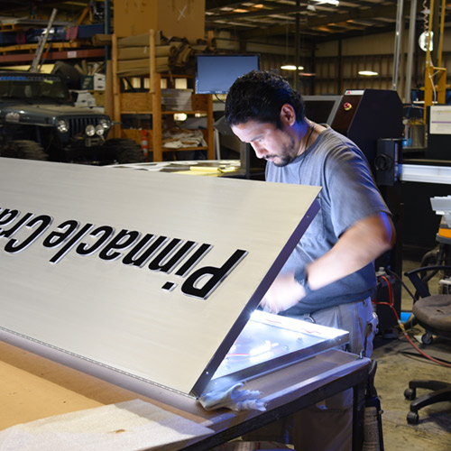 Assembly technician installing efficient LED lighting in a low-profile sign cabinet with push-through letters.