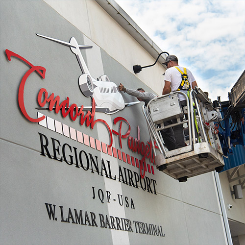 Casco Crew making final adjustments to a plate letter sign at Concord-Padgett Regional Airport.