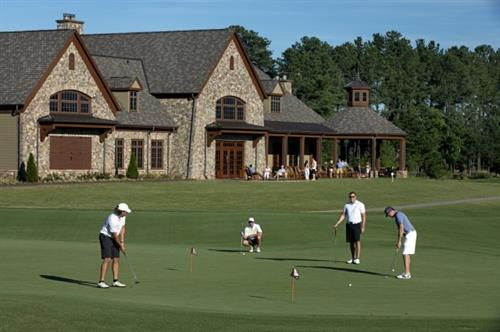 Golfers warm up on the practice putting green before teeing off.