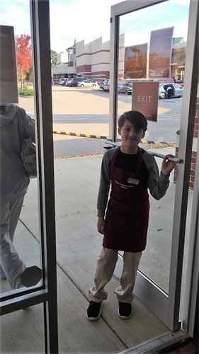 Adam holding doors for customers