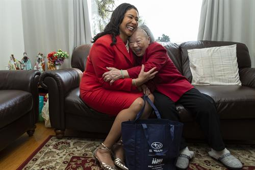 SF Mayor London Breed hugs senior client during March for Meals campaign