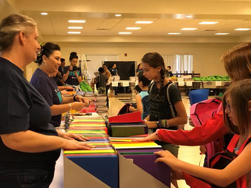 Back-to-School Brigade 2018 on Hickam AFB - Operation Homefront volunteers handing out school supplies to military children.