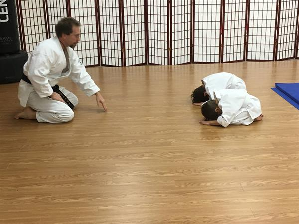Two junior students bowing at the end of a class
